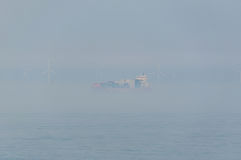 Navio de recipiente que passa um windpark a pouca distância do mar durante a névoa Fotos de Stock Royalty Free