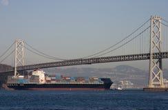 Navio de recipiente sob a ponte Fotos de Stock
