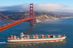 Navio de recipiente sob a ponte de porta dourada Imagem de Stock