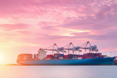 Navio do frete da carga do recipiente com a ponte de trabalho do guindaste no estaleiro no crepúsculo para a exportação logística imagens de stock royalty free