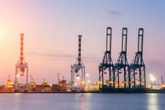 Navio do frete da carga do recipiente com a ponte de trabalho do guindaste no estaleiro no crepúsculo para a exportação logística Imagem de Stock Royalty Free
