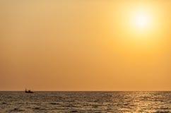 Navio pequeno da pesca no oceano infinito sob a luz solar ambarina Fotografia de Stock Royalty Free