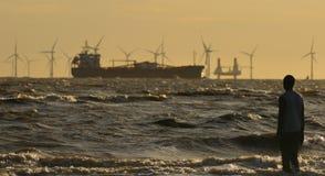 Navio que passa na frente da exploração agrícola de vento Fotos de Stock