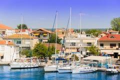 Navios de navigação no porto, no mar Mediterrâneo, na costa grega, ao lado das casas brilhantemente coloridas foto de stock