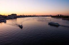 Navios pequenos no espaço de água do rio de Dnieper na cidade da noite Imagem de Stock