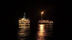 Navire de bateau-citerne de FPSO près d'installation de plateforme pétrolière la nuit Pétrole marin et industrie du gaz clips vidéos