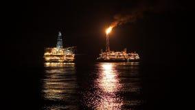 Navire de bateau-citerne de FPSO près d'installation de plateforme pétrolière la nuit Pétrole marin et industrie du gaz banque de vidéos
