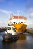 Navire porte-conteneurs avec le bateau de traction subite dans le blocage image stock