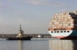 Navire porte-conteneurs et bateau de traction subite Images stock