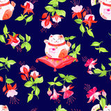 Navy background with chinese fuchsia and lucky cats sitting on t Stock Photo