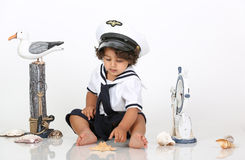 Navy beach boy. Picture of a baby dressed as Navy playing with props stock image