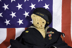 Navy Bear. Teddy bear in WWII navy uniform with metals in front of an American Flag Stock Image