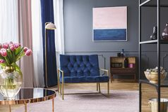 Navy blue armchair next to lamp in sophisticated apartment inter. Ior with painting and flowers. Real photo Stock Image