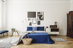 Navy blue bed with blanket next to cabinet with radio in retro bedroom interior with posters. Real photo. Concept stock photos