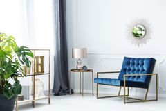 Navy blue elegant living room. Navy blue armchair next to table with gold lamp in elegant living room interior with mirror royalty free stock photography