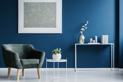 Navy blue living room interior. Green armchair against the wall with silver painting in navy blue living room interior with flowers royalty free stock photos