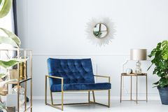 Navy blue living room. Navy blue armchair next to gold table with lamp against white wall with mirror in living room interior royalty free stock photo