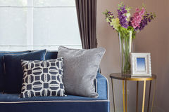 Navy blue modern classic sofa and retro, gray and blue pillows with a lovely orchid vase Royalty Free Stock Photo
