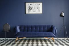 Navy blue room interior with comfortable plush couch in the midd. Le, black lamp and side table with decoration standing on chessboard floor. Framed image on the royalty free stock photos