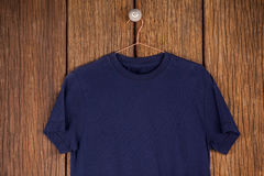 Navy blue t-shirt on hanger. On wood panelling royalty free stock photo