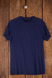 Navy blue t-shirt on hanger. On wood panelling Stock Image
