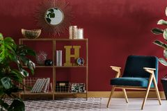 Red elegant livng room interior. Navy blue wooden armchair next to shelves against red wall with mirror in elegant living room interior stock photos