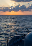 Navy cannon on sunset in the sea Stock Images