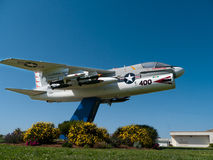 Navy fighter airplane near a base in California. Navy fighter airplane at a base in California USA ,green grass and yellow plants Royalty Free Stock Image