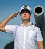 A navy officer standing under a ship`s cannon royalty free stock image