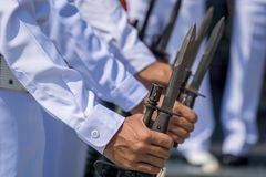 Navy officer in summer white uniform hold M16 rifle with bayonet. Preparing for salute VIP stock photography
