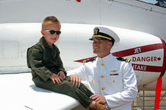 Navy pilots, young and old. Current and future navy pilots with a navy jet as the background Royalty Free Stock Images