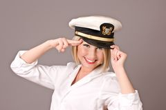Navy pinup girl. Blond navy pinup girl with officers hat saluting royalty free stock photos