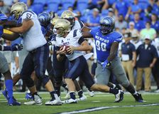 NAVY Quarterback  Zach Abey scrambles. NAVY Quarterback  Zach Abey 9 scrambles out of the pocket while being chased by Memphis Tigers Linebacker, BRAYLON BROWN Royalty Free Stock Photography