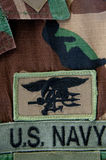 Navy SEAL trident on camoflauge. Uniform Stock Images