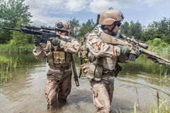 Navy SEALs. Crossing the river with weapons Royalty Free Stock Images