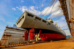 Navy ship repair. Gray color navy ship on dry dock for maintenance and repair stock photo