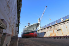 Navy ship repair. Gray color navy ship on dry dock for maintenance and repair royalty free stock photography