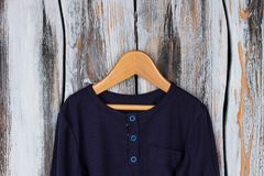 Navy top with blue buttons. And breast pocket on wooden hanger. Lightweight cotton shirt for boys and girls Stock Image