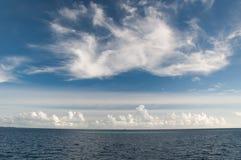 Nawadnia ocean indyjski z błękitną półksiężyc rafa koralowa, pod niebieskim niebem z vortex chmurami Obrazy Stock