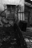 Nawiedzający dom z płotowymi i strasznymi okno Zdjęcia Royalty Free
