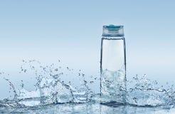 Nawilżanie szampon na błękitne wody tle z wiele dużymi pluśnięciami wokoło butelki Zdjęcia Royalty Free