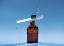 Nawilżanie wieka serum na błękitne wody tle z pipetą i kroplami Obraz Stock