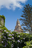 Naxxar parish church, viewed from Palazzo Parisio, Naxxar, Malta. Blue skies and lush green gardens, Naxxar parish church, viewed from Palazzo Parisio, Naxxar Royalty Free Stock Image