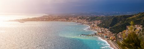 Naxxos, Sicily - Panoramic skyline view of Giardini Naxxos town and beach with turquoise sea water. And pine trees in front Royalty Free Stock Image