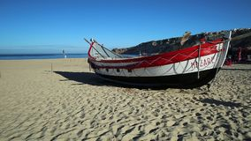 Nazare fishing boat. Nazare, Portugal - August 16, 2017: prospective view of colorful traditional old wooden fishing boats on the beach of fishing village of stock video footage