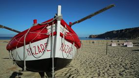 Nazare fishing boat. Nazare, Portugal - August 16, 2017: colorful traditional old wooden fishing boats on the beach of fishing village of Nazare. The fishing stock video footage
