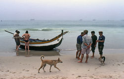 NAZARE,  PORTUGAL – JULY, 1981. A group of fishermen, helps take a boat from the sea after a day of fishing on July, 1981 in Nazare, Portugal Royalty Free Stock Photography
