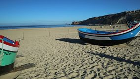 Nazare old fishing boat. Nazare, Portugal - August 16, 2017: colorful traditional old wooden fishing boat on the beach of fishing village of Nazare.The high stock video