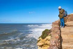 NAZARE, PORTUGAL - 1 DE FEBRERO DE 2018: El caminante femenino mira las ondas de la alta orilla imagenes de archivo