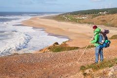 NAZARE, PORTUGAL - 1 DE FEBRERO DE 2018: El caminante masculino mira las ondas de la alta orilla fotos de archivo libres de regalías